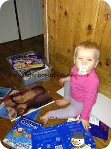 Baby surrounded by Christmas books
