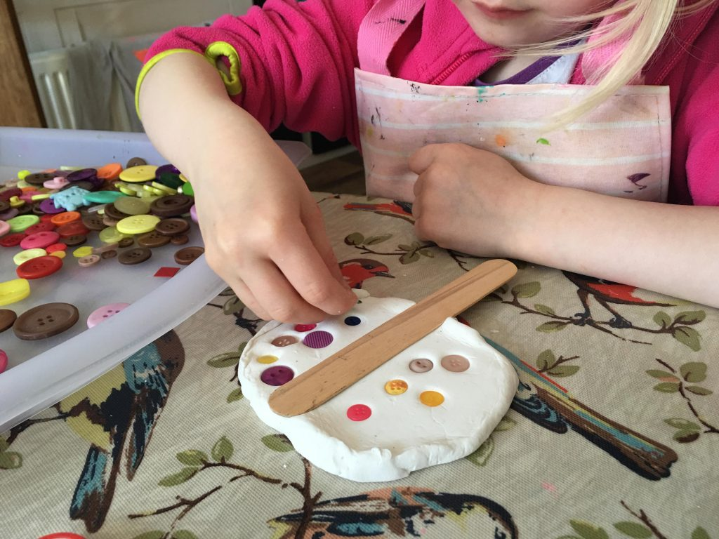 child pressing buttons into clay